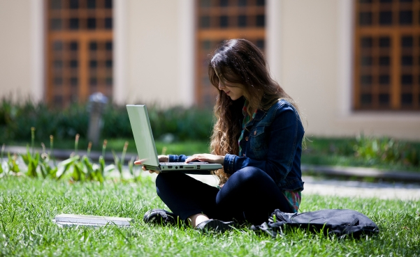 girl in grass with laptop